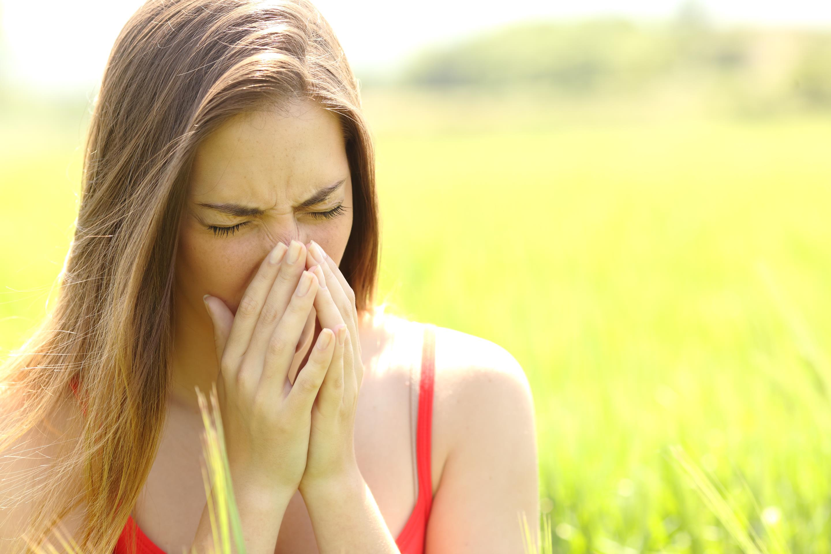 Woman with allergy coughing in a field.jpg